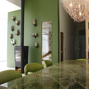 Idee per una sala da pranzo design di medie dimensioni con pareti verdi e stufa a legna