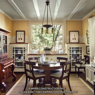 Cette image montre une salle à manger ouverte sur la cuisine craftsman de taille moyenne avec un mur jaune, un sol en bois brun et aucune cheminée.
