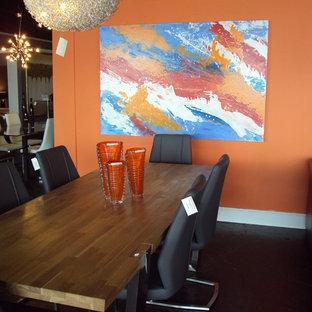 Réalisation d'une salle à manger design avec un mur orange et béton au sol.