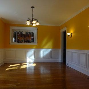 Esempio di una grande sala da pranzo chic chiusa con pareti arancioni, pavimento in legno massello medio e pavimento marrone