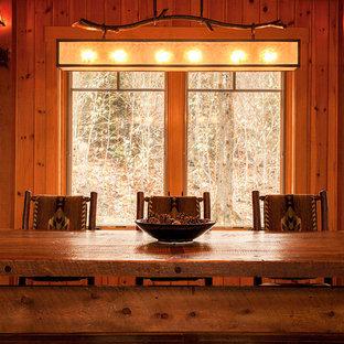 Idée de décoration pour une très grand salle à manger ouverte sur le salon chalet avec un mur marron, un sol en bois clair, une cheminée standard et un manteau de cheminée en pierre.