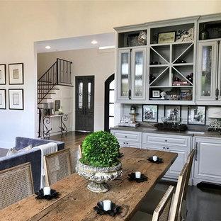 Ispirazione per una grande sala da pranzo aperta verso la cucina classica con pareti bianche, parquet scuro, camino classico, cornice del camino in pietra e pavimento marrone