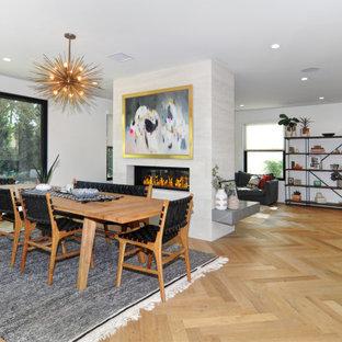 Idee per una sala da pranzo minimal con pareti bianche, parquet chiaro, camino lineare Ribbon e pavimento beige