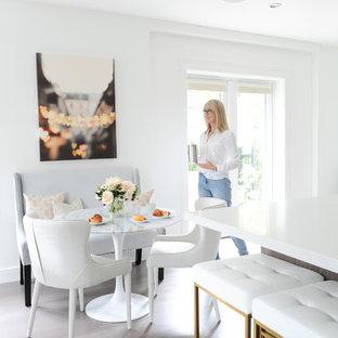 Imagen de comedor de cocina moderno, pequeño, sin chimenea, con paredes blancas y suelo de madera en tonos medios