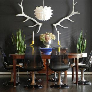 Immagine di una sala da pranzo eclettica con pareti nere e parquet scuro