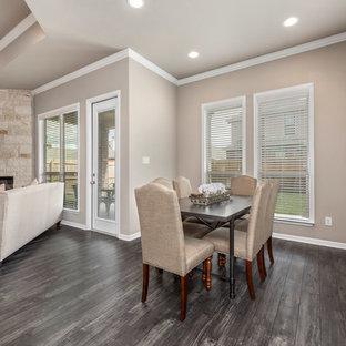 Esempio di una sala da pranzo aperta verso la cucina stile americano di medie dimensioni con pareti beige, pavimento in laminato, camino ad angolo, cornice del camino in pietra e pavimento multicolore