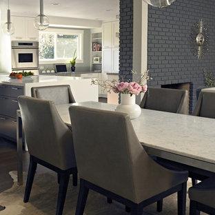 Ispirazione per una sala da pranzo aperta verso il soggiorno design di medie dimensioni con parquet scuro, camino classico, cornice del camino in mattoni e pareti grigie