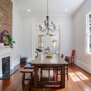 Modelo de comedor clásico, pequeño, cerrado, con paredes blancas, suelo de madera en tonos medios, chimenea tradicional, marco de chimenea de yeso y suelo marrón