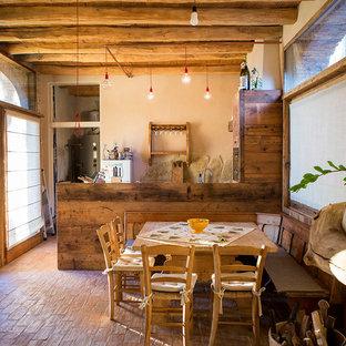 Ejemplo de comedor rural con paredes blancas y suelo de baldosas de terracota