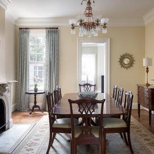 Foto di una sala da pranzo vittoriana chiusa con pareti beige, parquet scuro, camino classico, cornice del camino in cemento e pavimento marrone