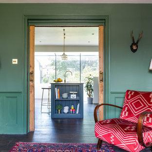 Esempio di una sala da pranzo aperta verso la cucina vittoriana di medie dimensioni con pareti verdi, parquet scuro, stufa a legna, cornice del camino in mattoni e pavimento marrone