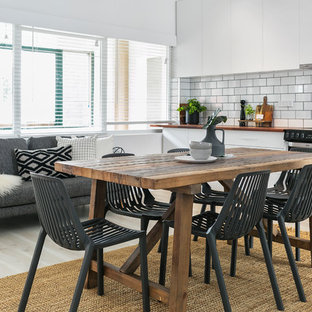 Design ideas for a contemporary kitchen/dining combo in Hobart with white walls and light hardwood floors.