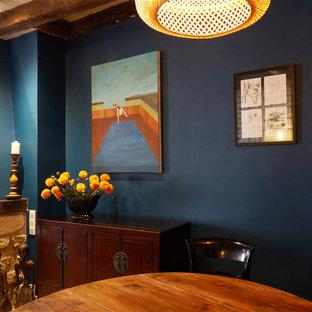 Modelo de comedor ecléctico, pequeño, con paredes azules, suelo de madera clara y marco de chimenea de madera