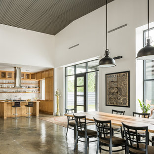 Design ideas for a large industrial kitchen/dining combo in Houston with white walls and concrete floors.