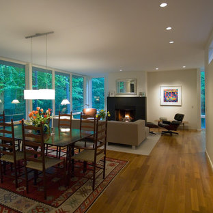 Modelo de comedor de cocina actual, grande, con paredes beige, suelo de madera clara, chimenea tradicional, marco de chimenea de hormigón y suelo marrón