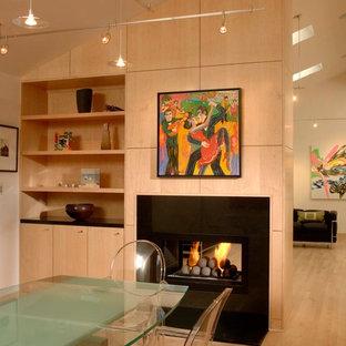Modernes Esszimmer mit hellem Holzboden, Tunnelkamin und Kaminsims aus Metall in Sonstige