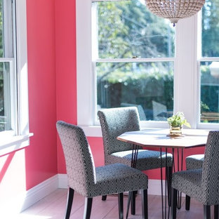 Ejemplo de comedor ecléctico con paredes rosas y suelo de baldosas de porcelana