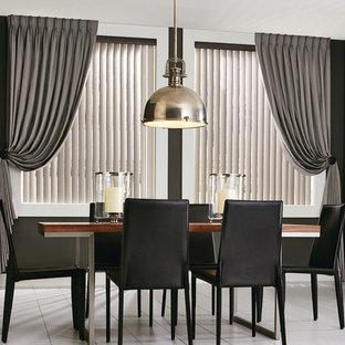 Immagine di una grande sala da pranzo aperta verso la cucina minimalista con pareti nere, pavimento in gres porcellanato e nessun camino