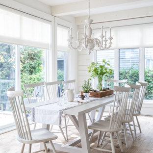 Cette image montre une grand salle à manger style shabby chic fermée avec un mur blanc, un sol en bois clair, aucune cheminée et un sol marron.