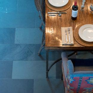 Ispirazione per una grande sala da pranzo aperta verso la cucina classica con pareti beige, pavimento in ardesia, camino sospeso, cornice del camino in cemento e pavimento grigio