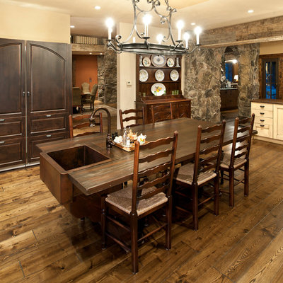 Example of a mountain style medium tone wood floor kitchen/dining room combo design in Denver with white walls