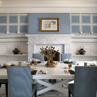 Immagine di una sala da pranzo chic chiusa e di medie dimensioni con pareti blu, pavimento in marmo, camino classico e cornice del camino in pietra