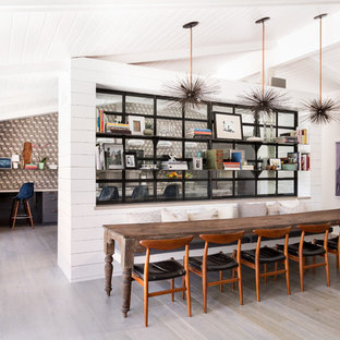 This is an example of a large midcentury kitchen/dining combo in Los Angeles with white walls, light hardwood floors and no fireplace.