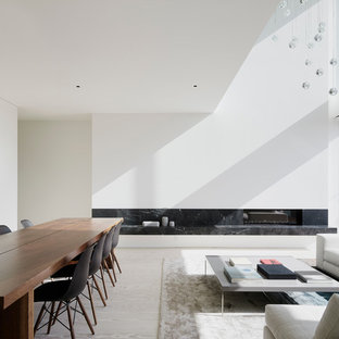 Modelo de comedor minimalista, de tamaño medio, abierto, con paredes blancas, suelo de madera clara, chimenea lineal y marco de chimenea de piedra