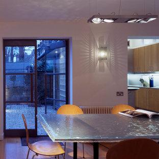 Foto di una sala da pranzo aperta verso il soggiorno mediterranea di medie dimensioni con pareti bianche, pavimento in legno massello medio, camino bifacciale e cornice del camino in legno