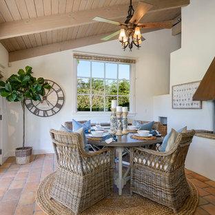 Idées déco pour une salle à manger bord de mer avec un mur blanc, un sol en carreau de terre cuite, une cheminée standard et un sol orange.