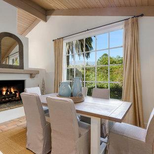 Inspiration pour une salle à manger marine avec un mur blanc, un sol en carreau de terre cuite, une cheminée standard et un sol orange.