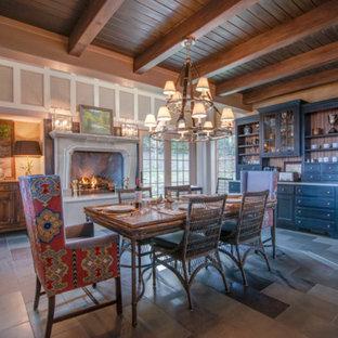 Ejemplo de comedor de cocina campestre, grande, con paredes beige, suelo de pizarra, chimeneas suspendidas, marco de chimenea de hormigón y suelo gris