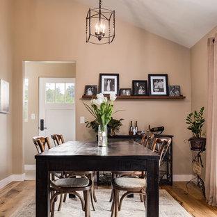 Foto di una grande sala da pranzo aperta verso il soggiorno country con pareti beige, pavimento in legno massello medio e pavimento blu