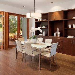 Стильный дизайн: гостиная-столовая среднего размера в современном стиле с белыми стенами, паркетным полом среднего тона, стандартным камином, фасадом камина из камня и коричневым полом - последний тренд
