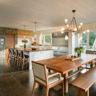 Esempio di una grande sala da pranzo aperta verso la cucina country con pareti beige, pavimento in ardesia, nessun camino e pavimento marrone