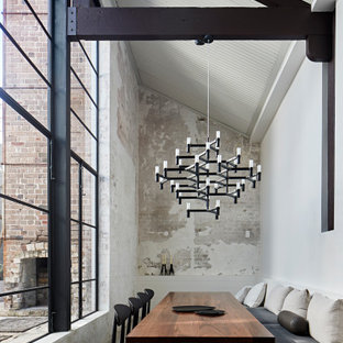 Photo of an industrial dining room in Sydney with white walls, concrete floors, no fireplace, grey floor, vaulted and brick walls.
