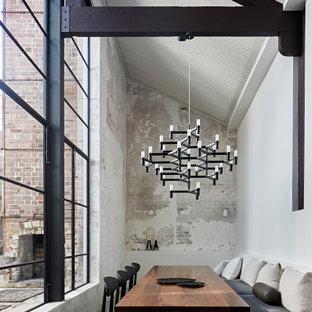 シドニーのインダストリアルスタイルのおしゃれなダイニング (白い壁、コンクリートの床、暖炉なし、グレーの床、三角天井、レンガ壁) の写真