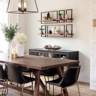 Ispirazione per una piccola sala da pranzo aperta verso il soggiorno country con pareti bianche, pavimento in laminato, camino classico e cornice del camino in mattoni