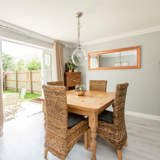 Small rural enclosed dining room in Dorset with grey walls, laminate floors and grey floors.