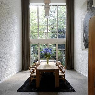 Modelo de comedor contemporáneo con paredes blancas y suelo de pizarra