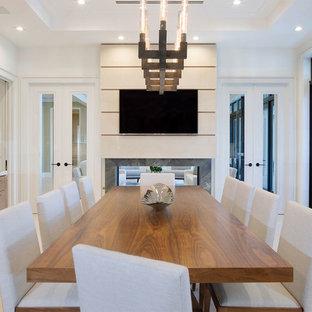 Foto di una sala da pranzo aperta verso la cucina di medie dimensioni con pareti bianche, pavimento con piastrelle in ceramica, camino bifacciale, cornice del camino in pietra e pavimento beige