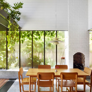 This is an example of a mid-sized contemporary open plan dining in Brisbane with white walls, concrete floors, a standard fireplace, a brick fireplace surround and grey floor.