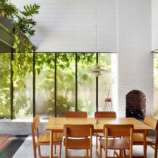 Idéer för en mellanstor modern matplats med öppen planlösning, med vita väggar, betonggolv, en standard öppen spis, en spiselkrans i tegelsten och grått golv