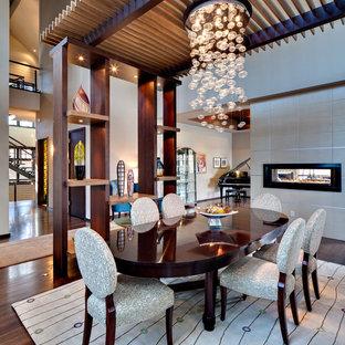 Новые идеи обустройства дома: большая кухня-столовая в современном стиле с серыми стенами, темным паркетным полом, двусторонним камином, фасадом камина из штукатурки и коричневым полом