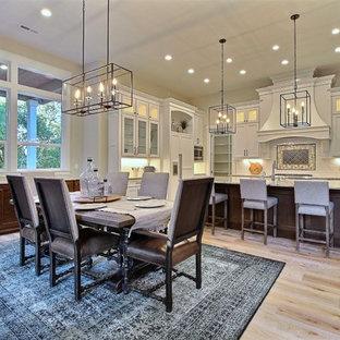 Idées déco pour une très grande salle à manger ouverte sur le salon classique avec un mur beige, un sol en bois clair, une cheminée standard, un manteau de cheminée en pierre et un sol beige.