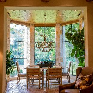 Immagine di una sala da pranzo stile rurale chiusa e di medie dimensioni con pavimento in mattoni, pareti beige e nessun camino