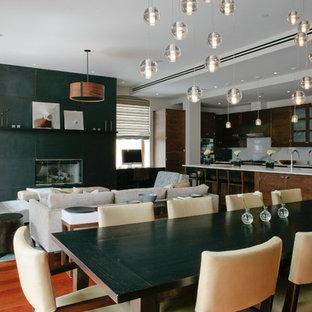 Cette image montre une salle à manger ouverte sur le salon design de taille moyenne avec un mur blanc, un sol en bois brun, une cheminée standard et un manteau de cheminée en béton.