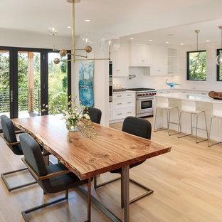 Réalisation d'une salle à manger ouverte sur la cuisine nordique avec un mur blanc et un sol en bois clair.