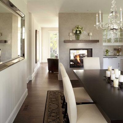 Elegant dark wood floor and brown floor enclosed dining room photo in Minneapolis with white walls, a two-sided fireplace and a plaster fireplace