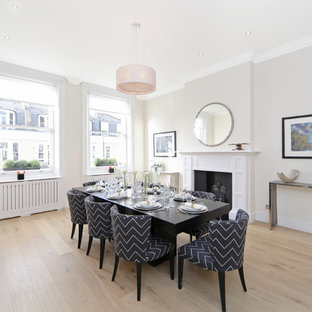 Example of a large trendy light wood floor kitchen/dining room combo design in London with a standard fireplace, a wood fireplace surround and beige walls